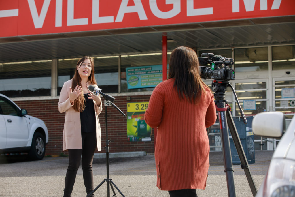 2020 ASF Fellow Katie Ellison speaking into a microphone in front of Village Market, located in the East Lake neighborhood of Birmingham.
